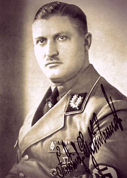 Portrait of Friedrich Hildebrandt wearing a Nazi uniform with a swastika armband. He has short, dark slicked-back hair and a small mustache.