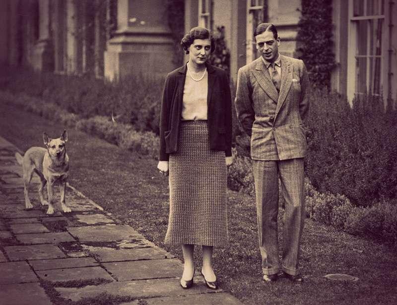 Marina and George walking alongside a tall Georgian mansion, followed by a medium-sized dog with tall ears.