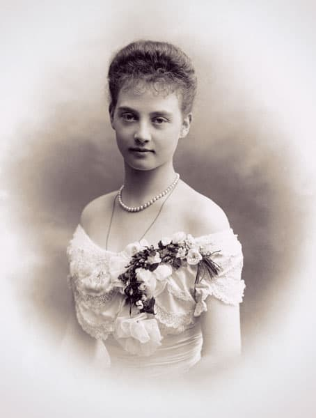 Alix in an off-the-shoulder pale dress with a large corsage at the neckline. She's wearing one strand of pearls and a gold chain.