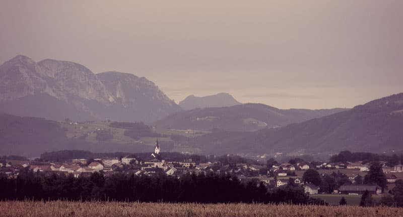 The village of Gmunden, nestled in a valley with rolling hills and then tall mountains in the background.