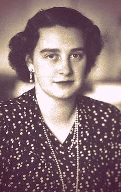 Alix's daughter Anastasia, dressed in a dark polka-dot dress with two pearl necklaces. She has short, curly dark hair.