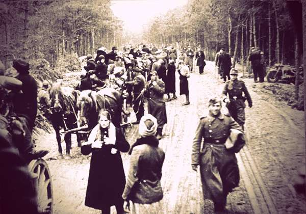 Refugees and soldiers fleeing East Prussia. They're walking on a dirt road through a dense forest. Some have horses and wagons.