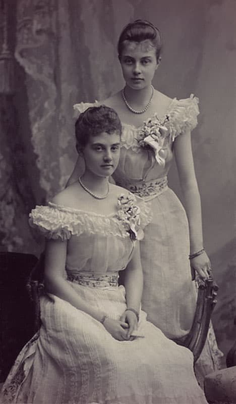 Alix and Olga wearing matching off-the-shoulder dresses with corsages, updos, and corsages on their bodices.