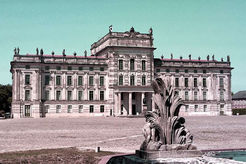 A tri-level neo-Renaissance palace with a large paved square in front of it, along with a decorative fountain.