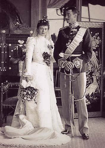 Alexandrine of Mecklenburg-Schwerin in a long-sleeved high-necked white wedding dress with Prince Christian of Denmark in an ornate military uniform including a saber.
