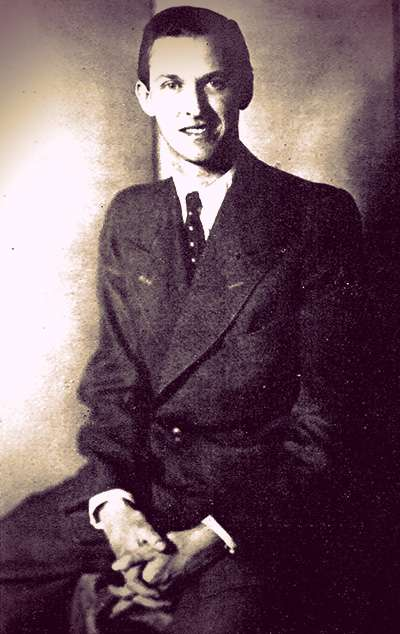 Paul Metternich dressed in a baggy dark suit and tie. He has short slicked-back hair and is smiling.