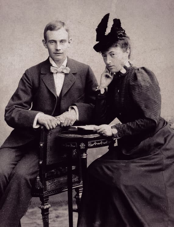 Friedrich Franz in a 3-piece suit and checkered bow tie with his mom, Anastasia, in a dark dress with leg-of-mutton sleeves and a tall hat with multiple plumes.