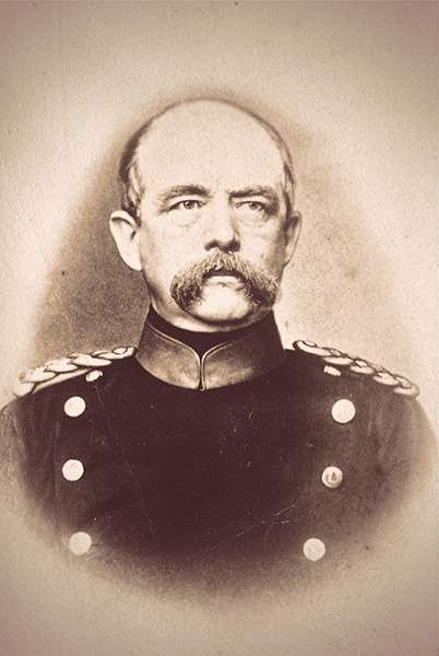 Otto von Bismarck as a middle-aged man wearing a military uniform. His mustache is bushy and droopy, hanging halfway to his chin.