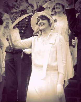 Ann-Mari von Bismarck wearing a white dress and hat, waving in a crowd of spectators at an event.