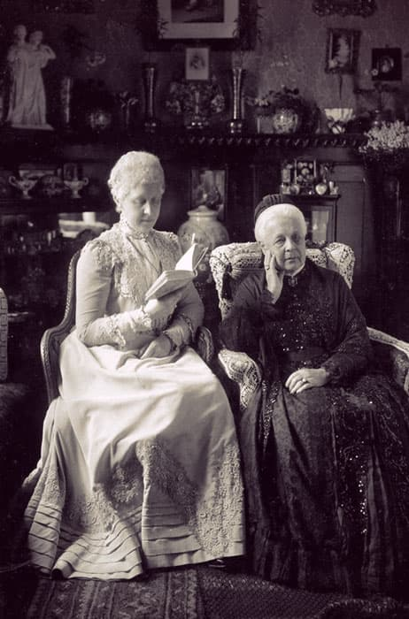 Princess Marie of Hanover in a pale lace-trimmed day dress reading a book next to her mom, Queen Marie of Hanover.