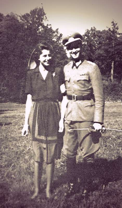Tatiana and Paul Metternich standing in a grassy field. He's wearing a military uniform and she's wearing a plain dark blouse and knee-length skirt.