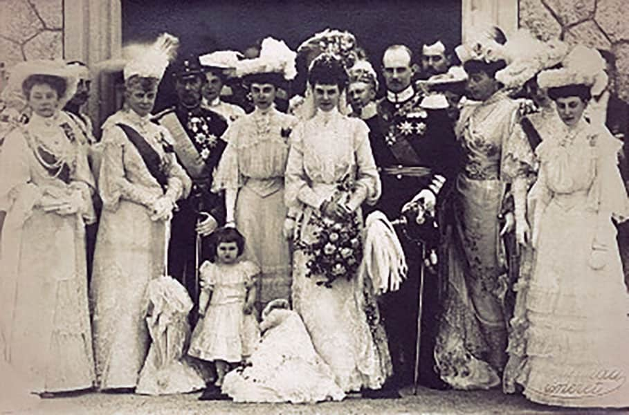 Alix in a high-necked long-sleeved white wedding dress. Friedrich Franz is in a military uniform. He holds his saber and helmet.