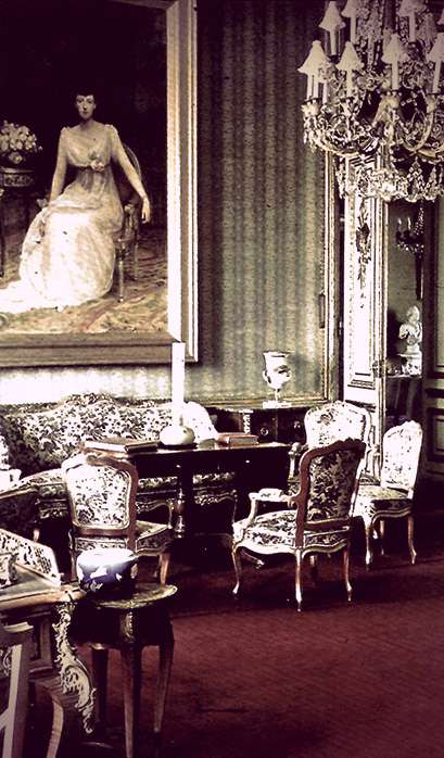 Photo of a living room with brocade sofas and chairs, a large crystal chandelier, and a very large painting on the far wall of Anastasia Mikhailovna in a soft white Grecian-style dress.