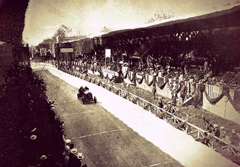 Decorated grandstands beside a racing straightaway with a 1904 racing car zooming down the homestretch.
