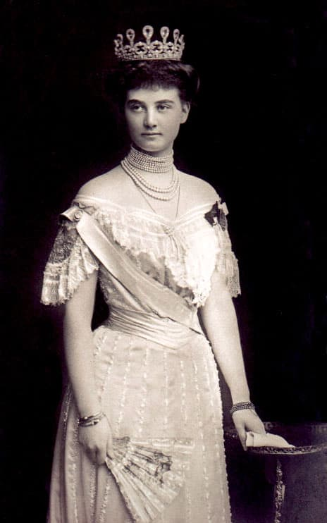 Alexandra of Mecklenburg-Schwerin in a pink dress, pearl necklaces, and this diamond and aquamarine tiara. She's holding a fan.