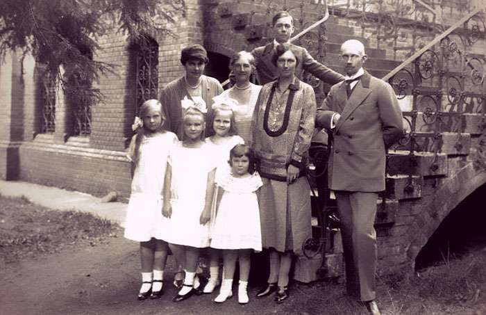 A family portrait on the steps of their hunting lodge. The women are in knee-length dresses, with short, waved hair.