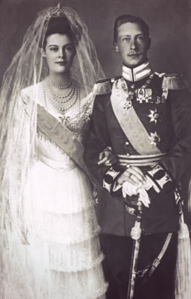 Cecilie in an off-the-shoulder white wedding dress - her arm is linked with  Wilhelm's. He wears a military uniform.