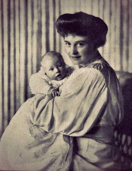 Alexandra of Mecklenburg-Schwerin in a pale dress holding her baby, dressed in a long christening gown.