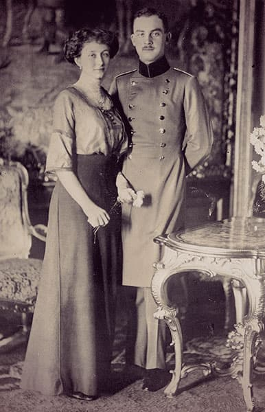 Viktoria Luise holding a rose, standing beside Ernst August, dressed in a military tunic.