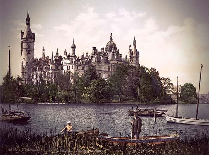 Schloss Schwerin bordered by a lake with several small boats around it.