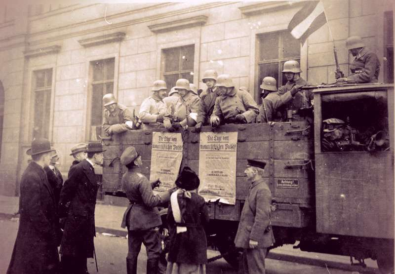 A military truck with a dozen men in the back. The truck bed has propaganda messages affixed to the sides. People on the street have gathered to read the messages.