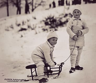 Two boys in white winter gear playing outside in the snow with a sled - the sons of Alexandra of Mecklenburg-Schwerin.
