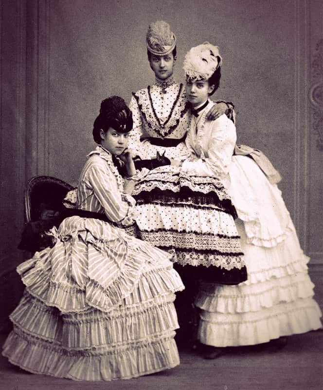 Thyra, Alix, and Dagmar posed together, wearing ruffled day dresses and hats with small plumes.