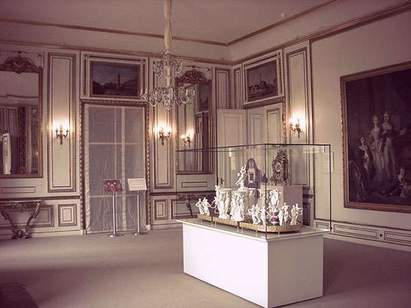 A gilded room in a palace with a glass vitrine housing small sculptures and objets d'art.