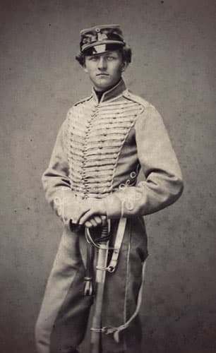 Marcher in his cavalry uniform, with lots of braiding on the jacket and cap. He has pale eyes and thick blond hair.