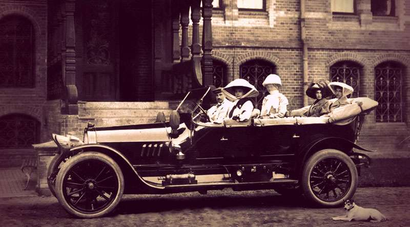Alix seated in the back of an early 1900s vehicle. Her sister-in-law is in the driver's seat.