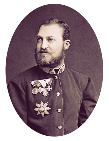 Ernst August in a simple military uniform with four medals. He has short, dark hair, a full, short beard. and a curved mustache.