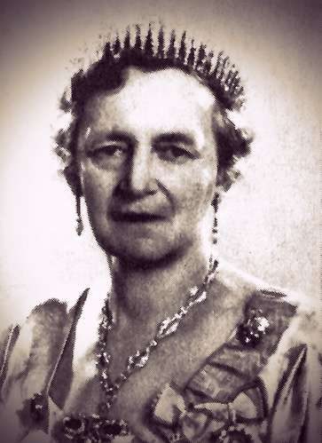 Photo of Queen Alexandrine as a middle-aged woman. She has short medium-blonde hair and is wearing a fringe tiara and formal gown with orders.