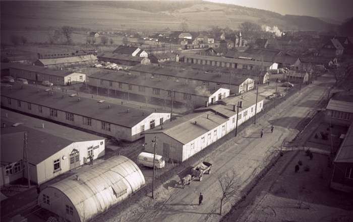 Photo of the camp, showing rows of barracks and temporary buildings. On the road nearby, someone is passing through with a horse-drawn wagon.