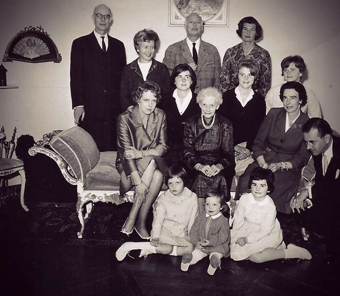 Group photo of Alix and her family. She's a white-haired old woman in the center of the photo, with the adults posed around and behind her and the kids on the floor in front.