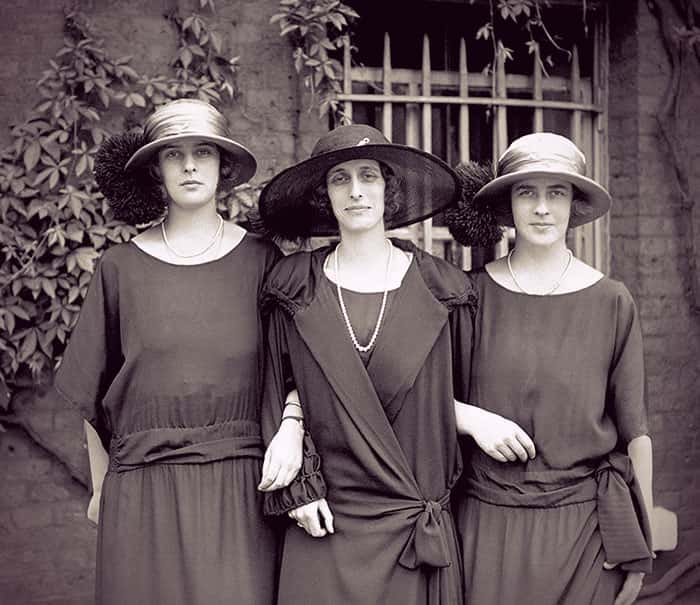 Princesses Theodora and Margarita standing on either side of Lady Louise Mountbatten, arms linked. They're all in large hats and simple, flowing dark colored dresses.