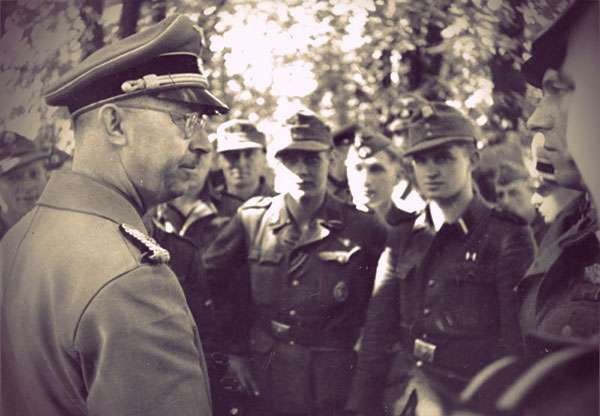 Heinrich Himmler and soldiers. Himmler is in his SS uniform, standing in profile. He is wearing glasses.
