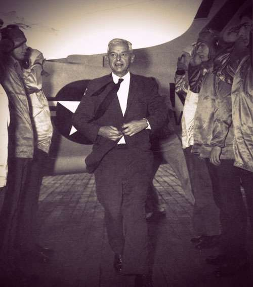 Paul NItze walking between two rows of Air Force crewmen. He's wearing a dark suit, white shirt, black tie, and smiling. He has short white hair.