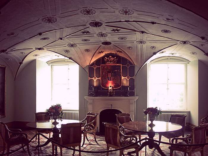 Schloss Glücksburg's RoterSaal. It has an arched roof with ceiling medallions, a fireplace, and several tables with dining chairs.