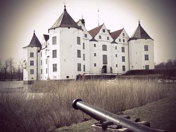 Exterior view of Schloss Glücksburg, with a cannon aimed at it.