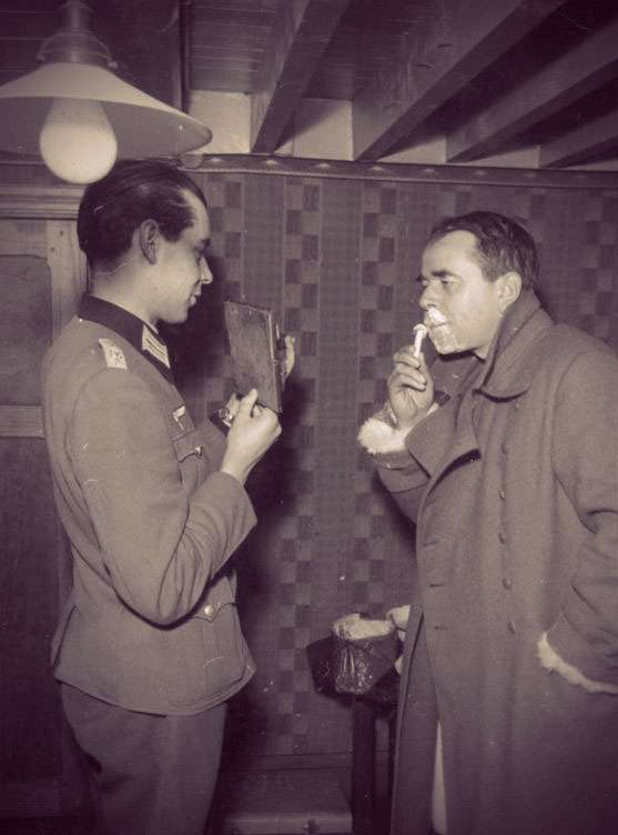Photo of Albrecht Speer shaving as he's fully dressed. An assistant holds a mirror in front of him.