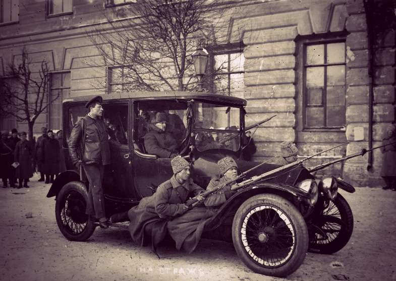 Revolutionary soldiers perched on the sides of a car, driving through Petrograd.