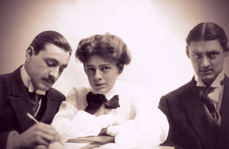 John, Ethel, and Lionel Barrymore sitting together at a table. Ethel and Lionel are looking at the camera. John is writing with a pencil.