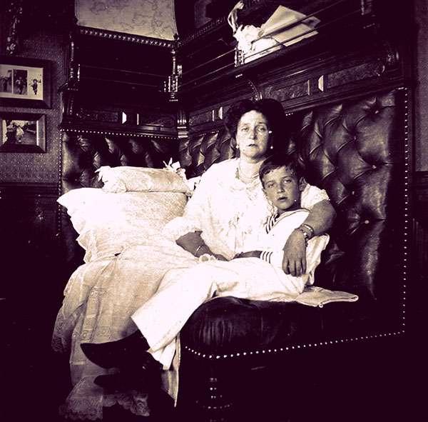 Empress Alexandra and Tsarevich Alexei sitting together on a sofa.