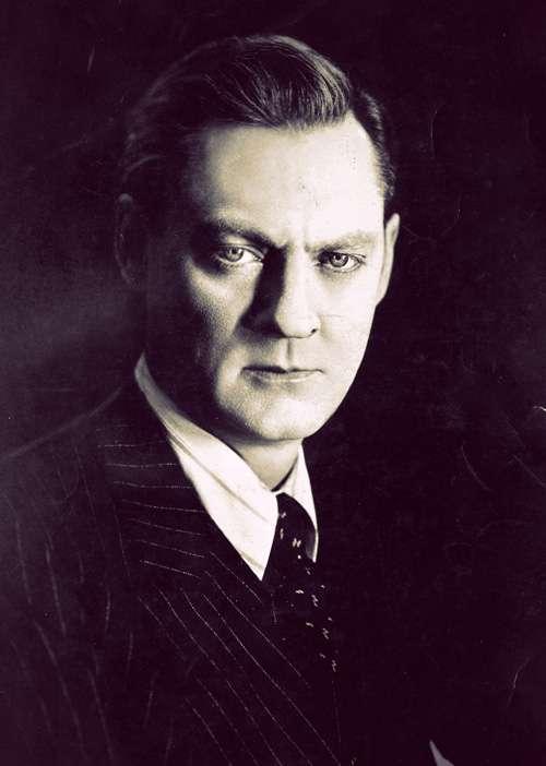 Lionel Barrymore in a dark pinstriped suit. His dark blonde hair is slicked back.