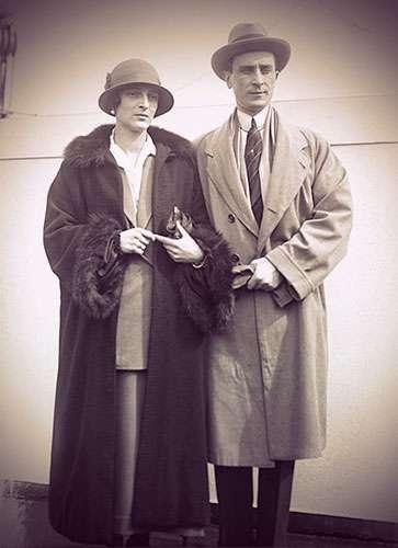Felix and Irina Yusupova in casual traveling clothes, coats, and hats.