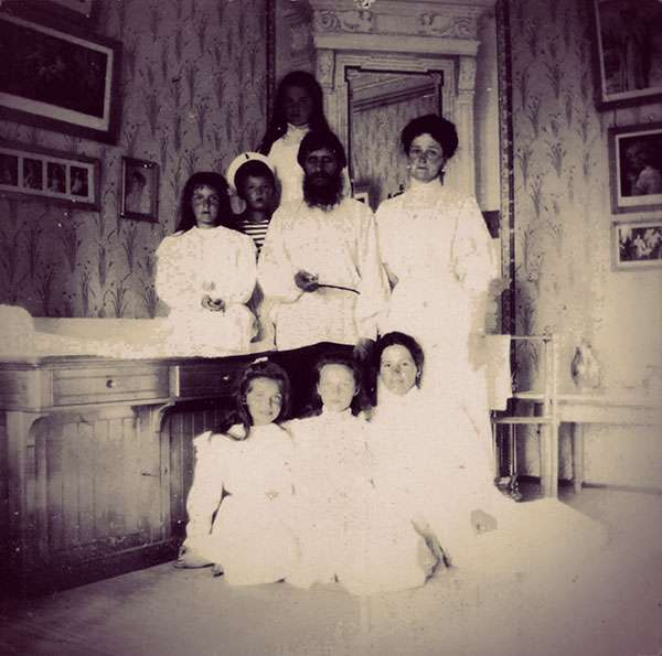 Alexandra with her kids and their governess. Rasputin stands with them in the middle of the photograph.
