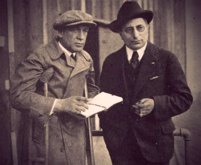 Louis B. Mayer in a suit, glasses, and hat on the set with one of his directors. He's holding a large cigar.
