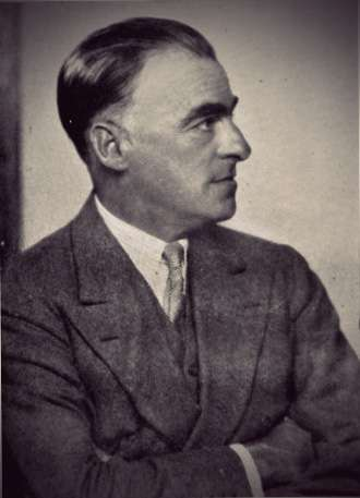 Sir Patrick Hastings in profile, wearing a gray 3-piece suit.