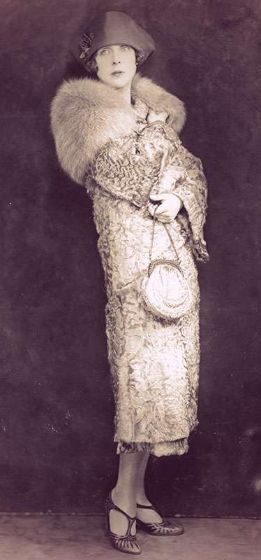 Full-length photo of Lady Diana Cooper wearing a fur-trimmed coat, cloche hat and t-strap sandals.