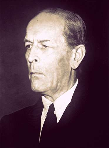 Close-up photo of Sir William Jowitt in a dark suit and tie. He's an older man, with a small mouth, hooded eyes, and a receding hairline.